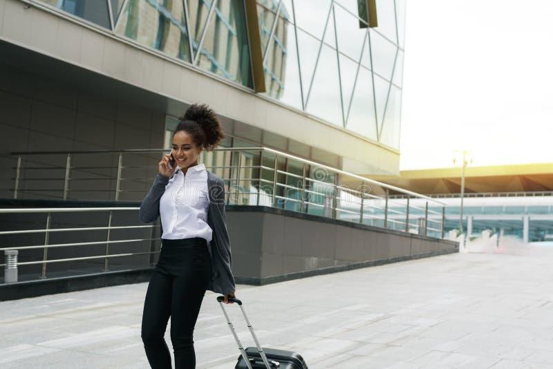Junge Frau mit Gepäck gehend am Anschluss stockfoto