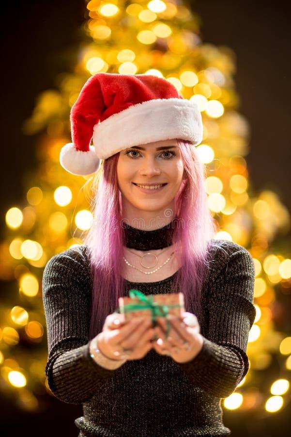 Junge Frau mit Geschenk, Weihnachtsbaum und dekorativem Beleuchtung bokeh Hintergrund Elfe und Fichte mit Dekorationen lizenzfreie stockfotos