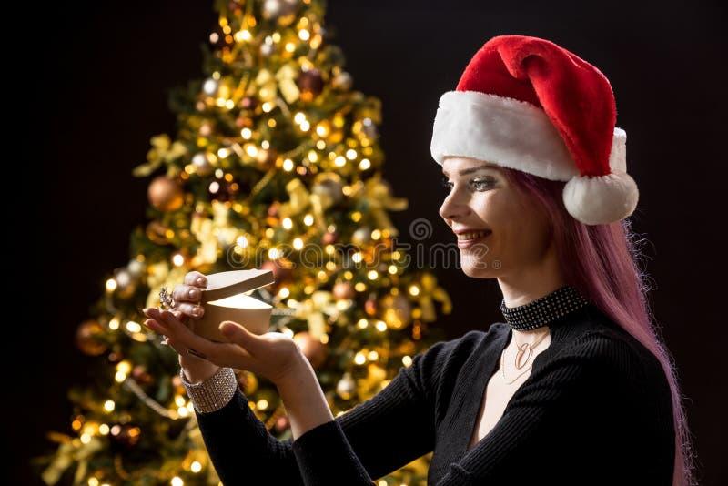 Junge Frau mit Geschenk, Weihnachtsbaum und dekorativem Beleuchtung bokeh Hintergrund Elfe und Fichte mit Dekorationen stockbild