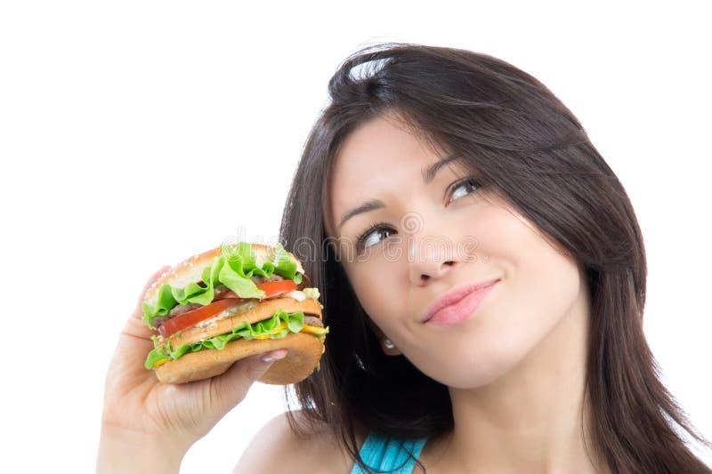 Junge Frau mit geschmackvollem ungesundem Burger des Schnellimbisses stockbild