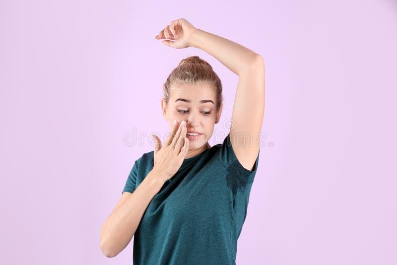 Junge Frau mit geschwitztem Fleck auf ihrer Kleidung gegen Farbhintergrund lizenzfreie stockfotografie