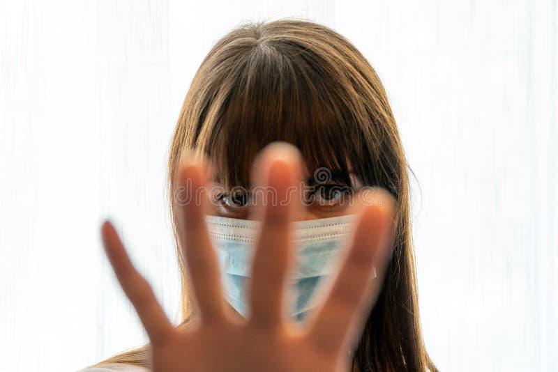 Junge Frau mit Gesichtsmaske, die die Handgedanken aufrecht hält, während sie durch die Kluft zwischen ihren Fingern schaut lizenzfreies stockbild