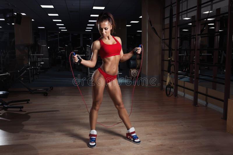 Junge Frau, mit gesunder sportlicher Zahl mit Springseil in der Turnhalle lizenzfreie stockbilder