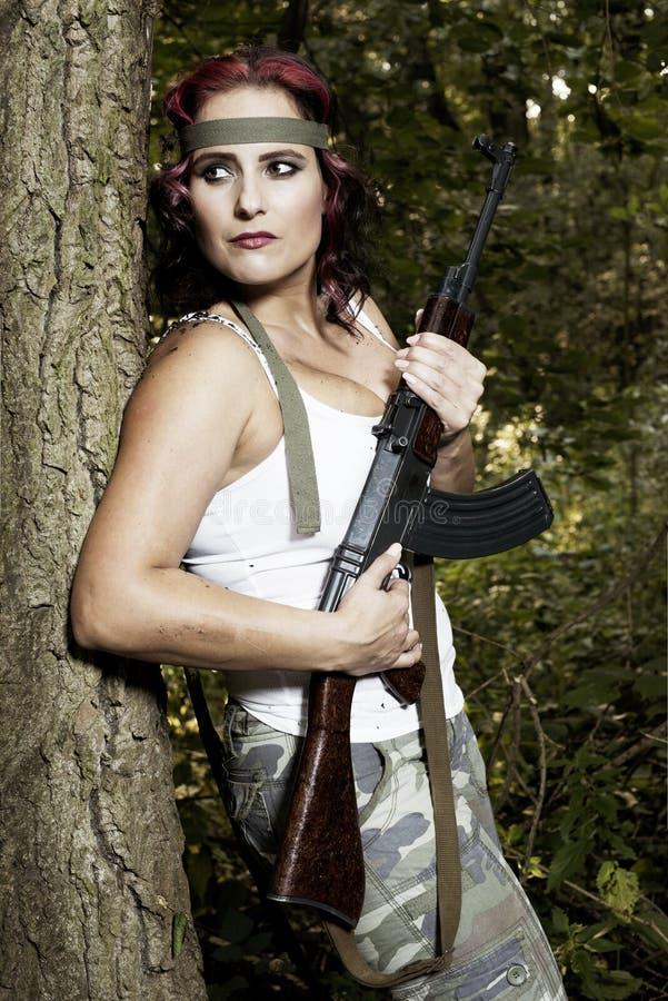 Junge Frau mit Gewehr stockbilder