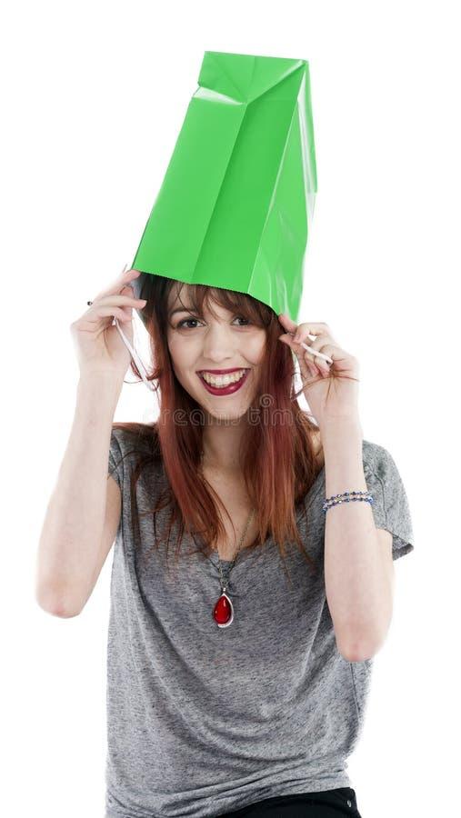 Junge Frau mit grüner Einkaufstasche auf Kopf stockfoto