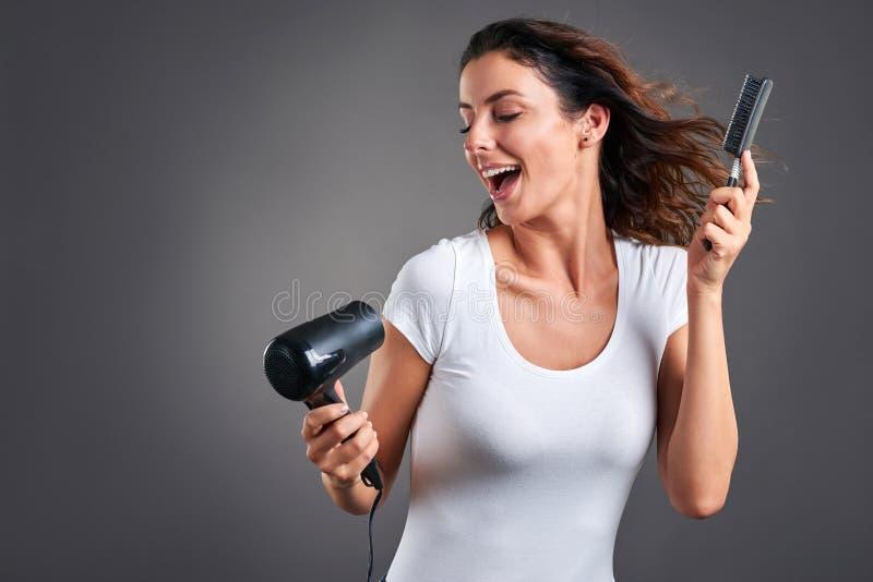 Junge Frau mit hairdryer lizenzfreie stockfotos