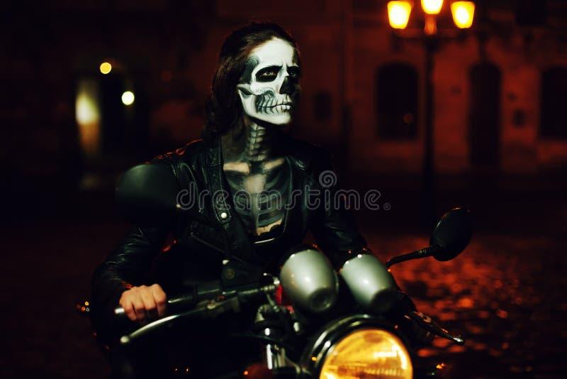 Junge Frau mit Halloween-Make-up, das auf dem Motorrad sitzt Straßen-Porträt stockfoto