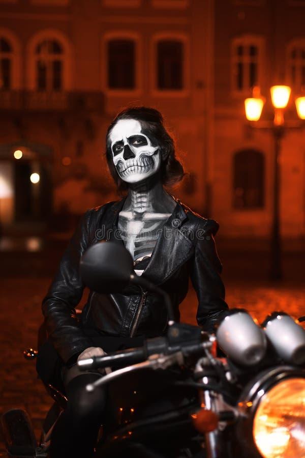 Junge Frau mit Halloween-Make-up, das auf dem Motorrad sitzt Straßen-Porträt stockfotos