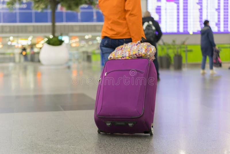 Junge Frau mit Handgepäck im internationalen Flughafenabfertigungsgebäude, das Informationsbrett betrachtend und überprüfen ihren stockfotos