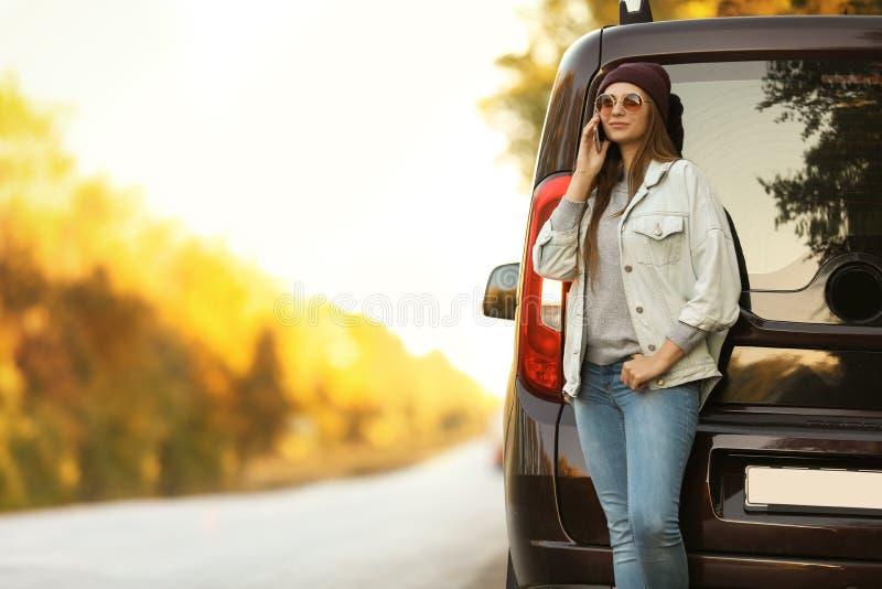 Junge Frau mit Handy nahe Auto lizenzfreie stockfotografie
