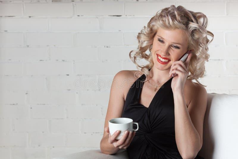 Junge Frau mit Handy und Tasse Kaffee. lizenzfreie stockfotografie