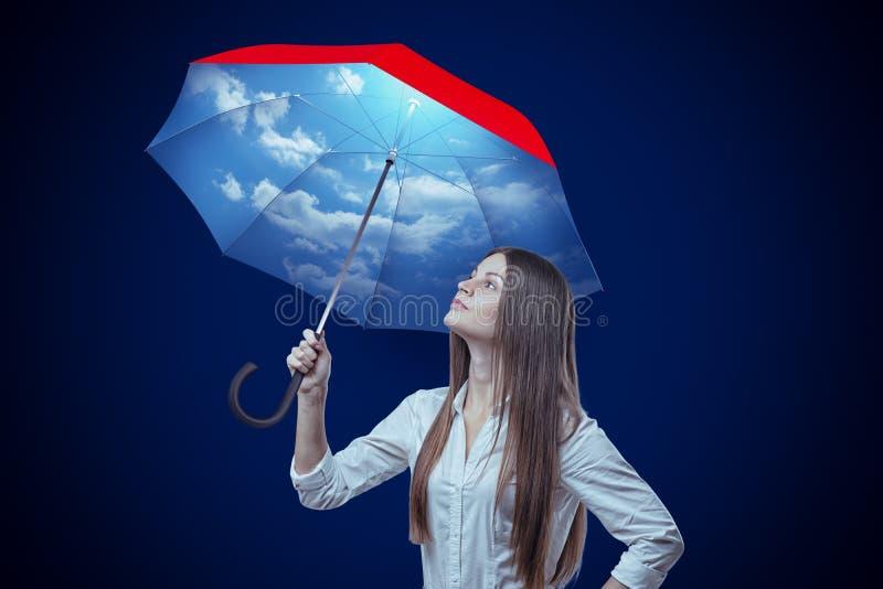 Junge Frau mit Himmelentwurfsregenschirm auf dunkelblauem Hintergrund lizenzfreies stockbild