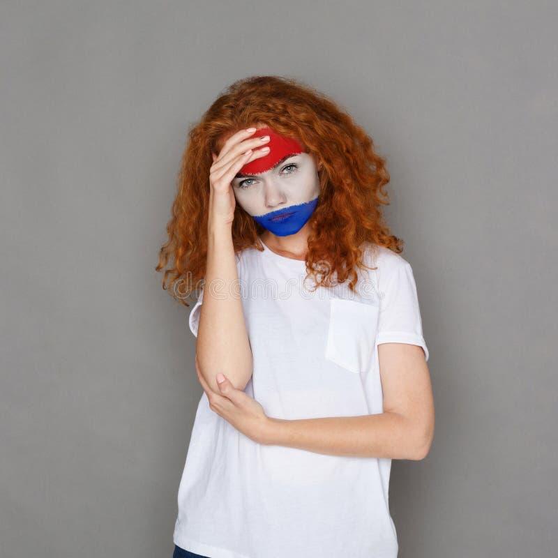 Junge Frau mit Holland-Flagge gemalt auf ihrem Gesicht stockfoto
