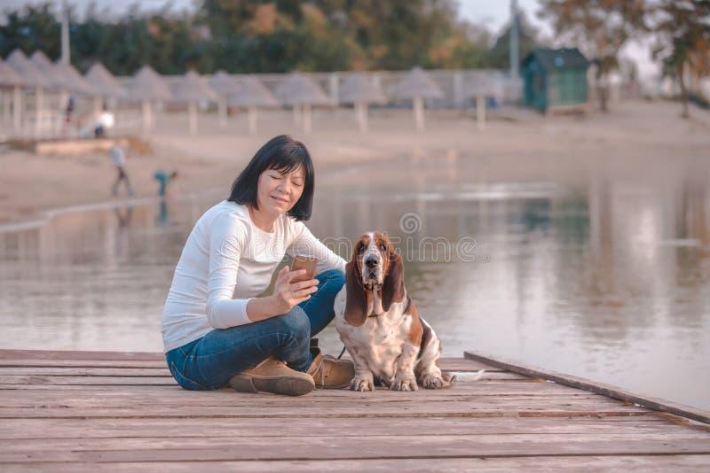 Junge Frau mit Hund unter Verwendung des intelligenten Telefons lizenzfreies stockbild