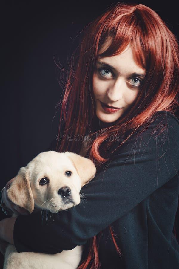 Junge Frau mit ihrem Labrador Retriever Hund auf schwarzem Hintergrund lizenzfreie stockfotos
