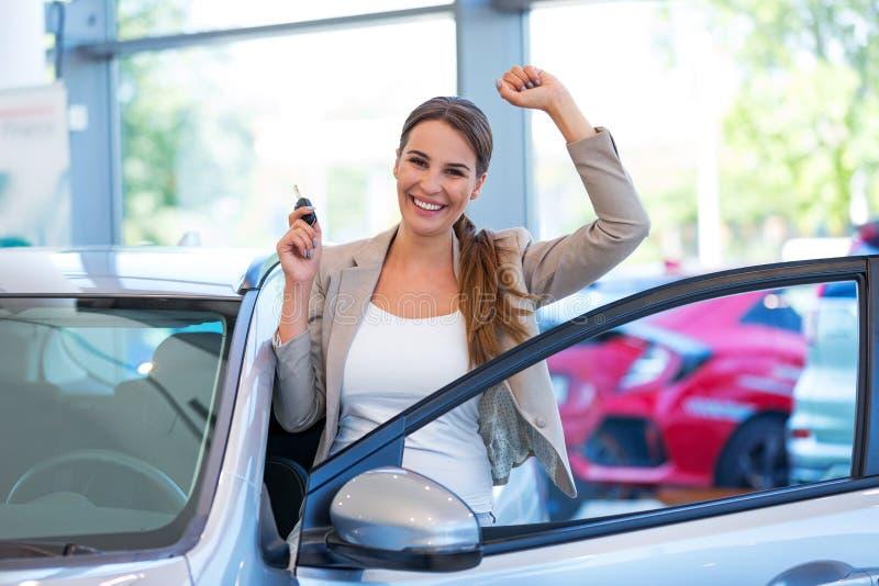 Junge Frau mit ihrem Neuwagen stockfotos