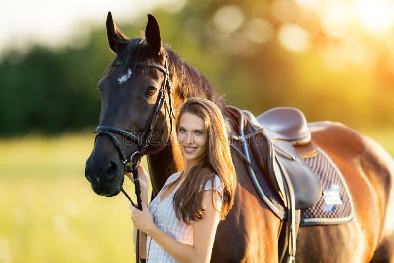 Junge Frau Mit Ihrem Pferd Im Abendsonnenunterganglicht