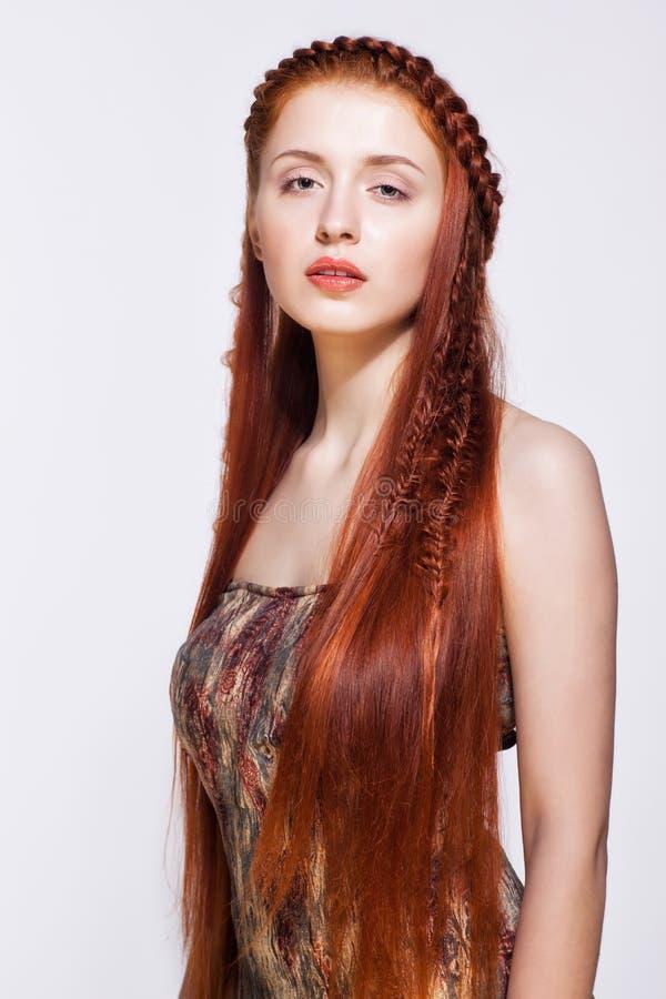 Junge Frau mit Ingwer flicht Frisur auf weißem Hintergrund lizenzfreies stockbild