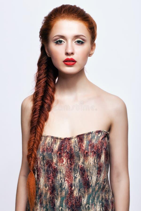 Junge Frau mit Ingwer flicht Frisur auf weißem Hintergrund lizenzfreie stockfotos