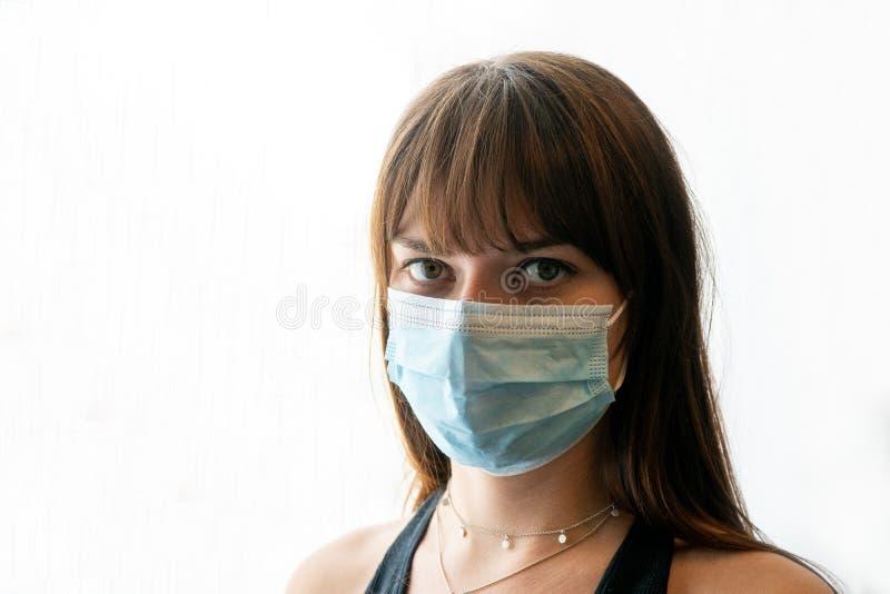 Junge Frau mit Kamera mit leichter chirurgischer Maske und hellem Hintergrund stockfoto