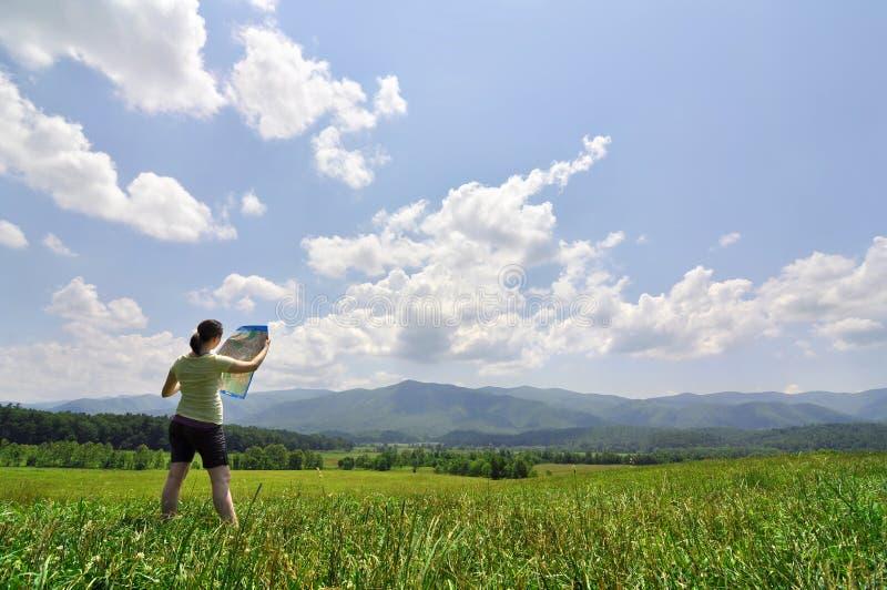 Junge Frau mit Karte eine beträchtliche Wildnis erforschend lizenzfreie stockfotos