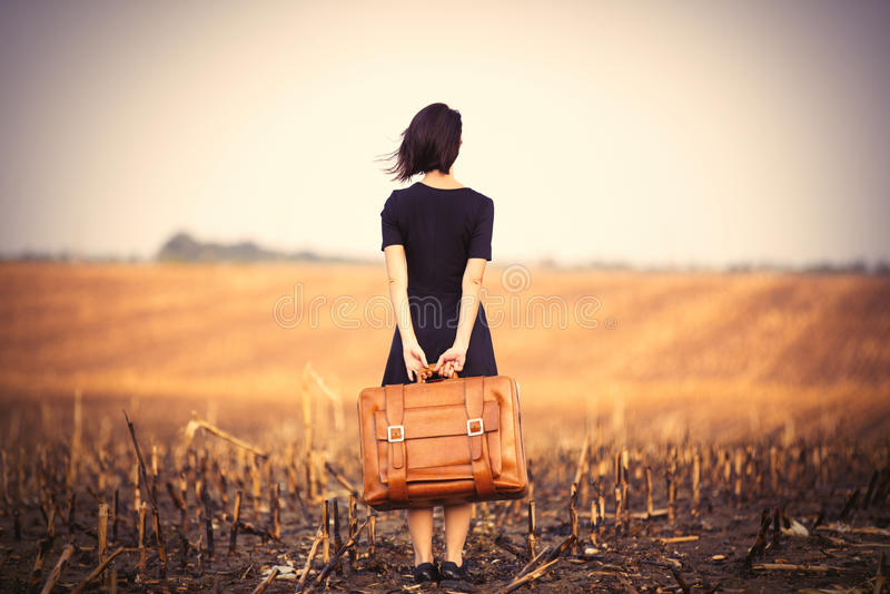 Junge Frau mit Koffer stockbilder