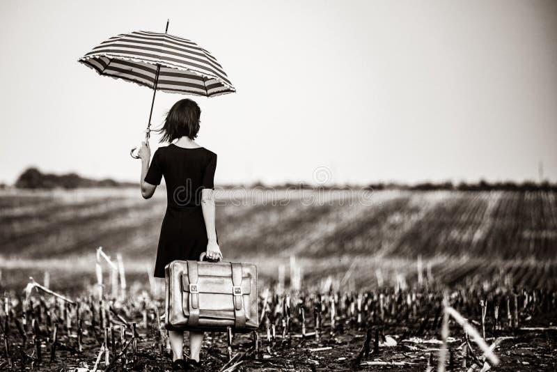 Junge Frau mit Koffer und Regenschirm stockfotografie