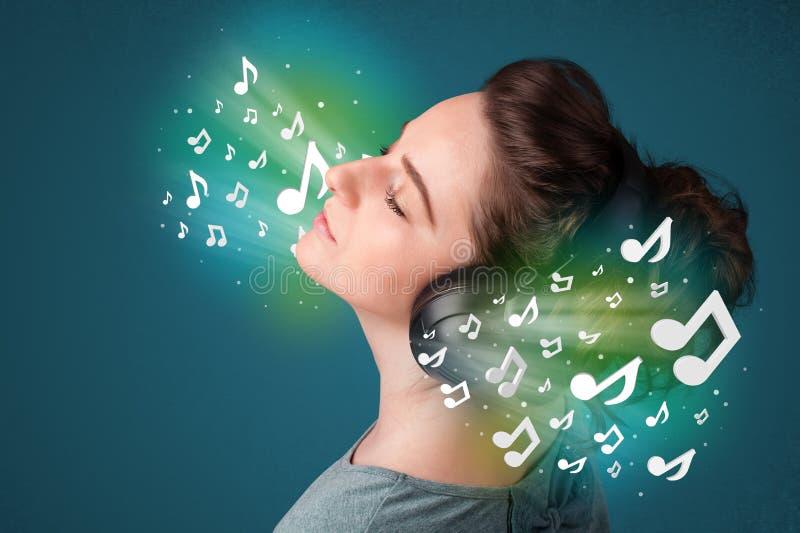 Junge Frau mit Kopfhörern hörend Musik lizenzfreies stockbild