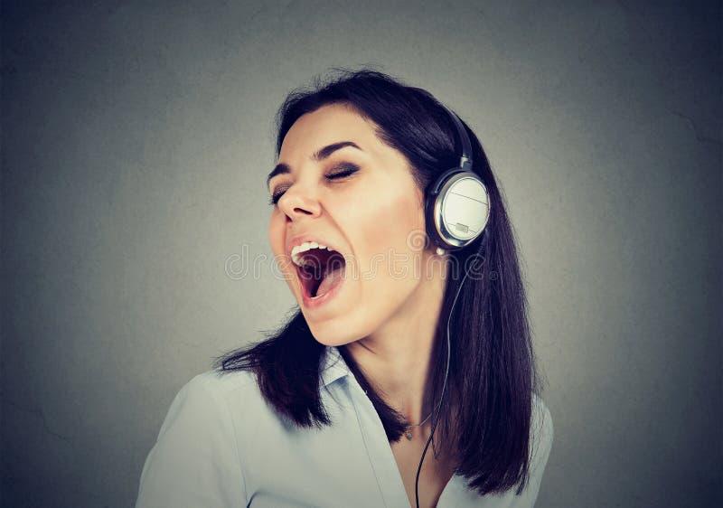 Junge Frau mit Kopfhörern singend lizenzfreies stockbild