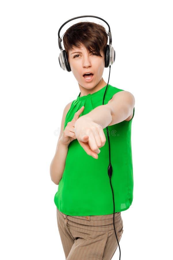 Junge Frau mit Kopfhörern zeigend auf Sie auf einem Weiß stockbild