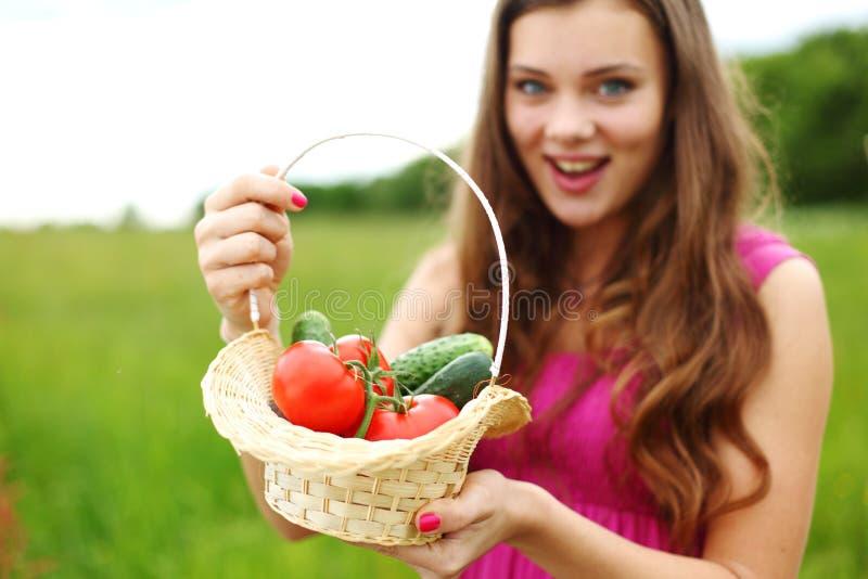 Junge Frau mit Korb des Gemüses lizenzfreie stockbilder