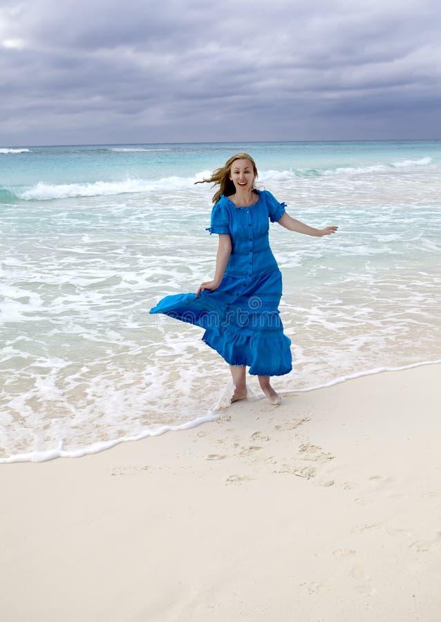 Junge Frau mit langen Haaren, die im Wind in einem blauen Kleid entlang des Meeresufers flattern, Kuba, Varadero stockfotografie