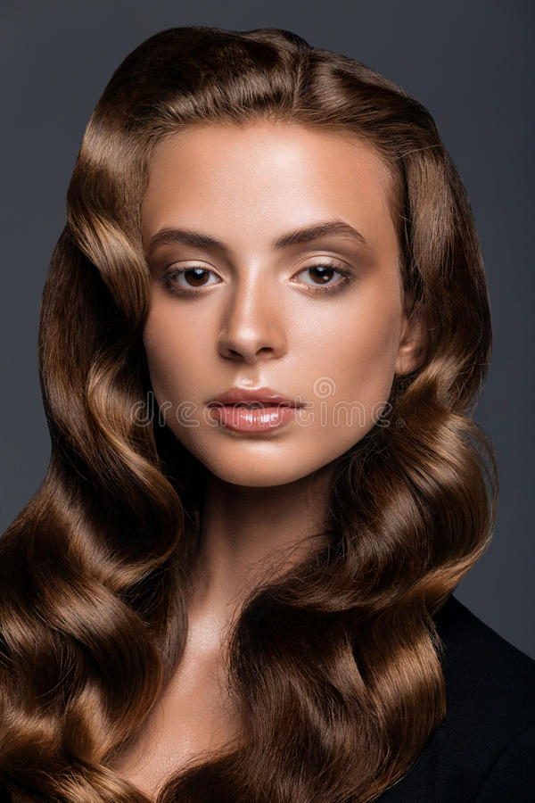 Junge Frau mit langer glatter gelockter Frisur lizenzfreies stockbild