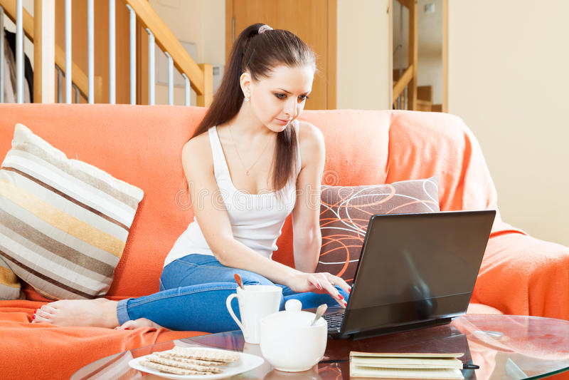 Junge Frau mit Laptop auf Sofa stockfotos