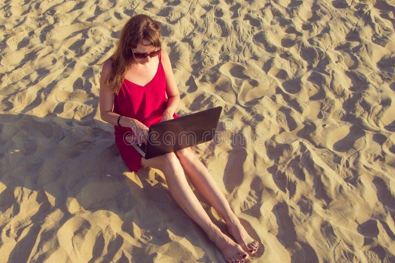 Junge Frau mit Laptop-Computer auf dem Strand Herunterschalten und lizenzfreies stockfoto