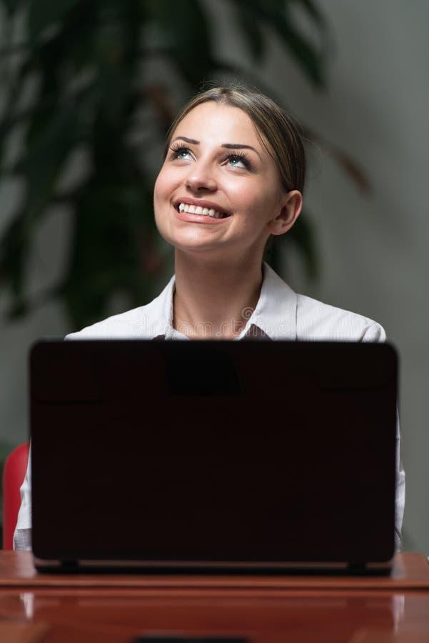 Junge Frau mit Laptop im Büro stockbild