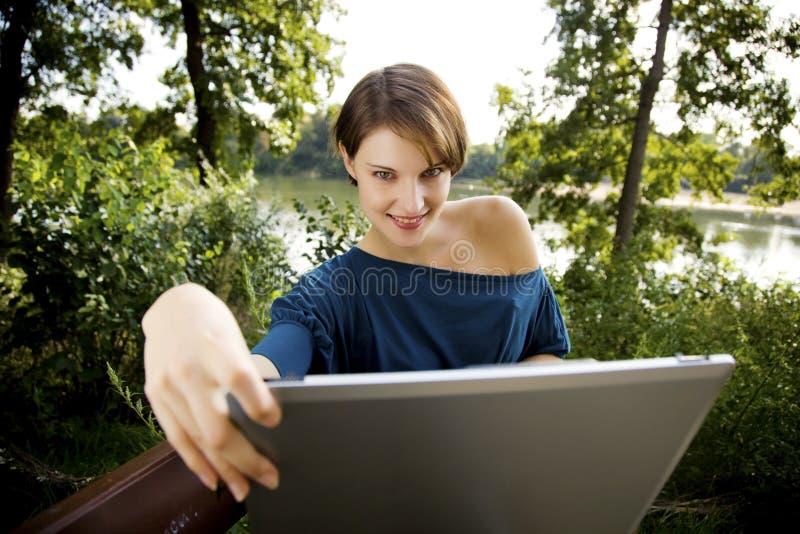 Junge Frau mit Laptop im Park lizenzfreies stockbild