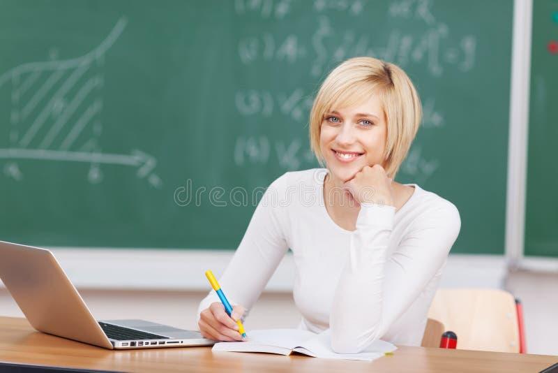 Junge Frau mit Laptop-Schreibens-Anmerkungen am Schreibtisch lizenzfreies stockfoto