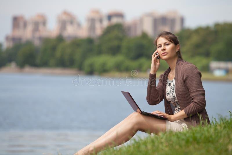 Junge Frau mit Laptop und Handy im Park. stockfotografie