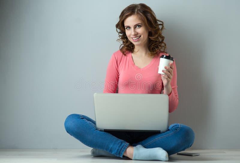 Junge Frau mit Laptop und Tasse Kaffee lizenzfreie stockbilder