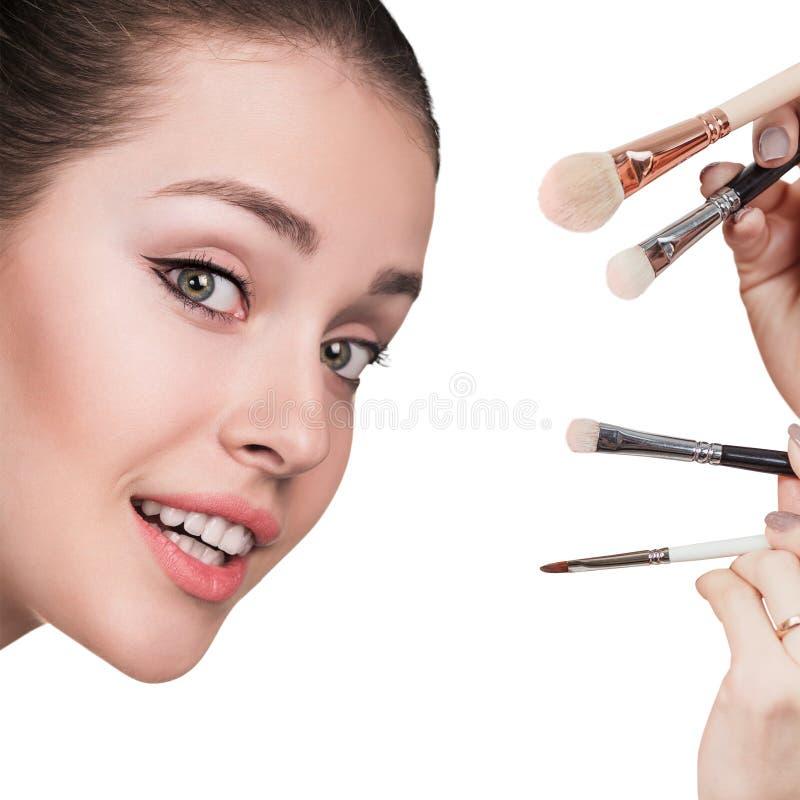 Junge Frau mit Make-upbürsten lizenzfreie stockfotos