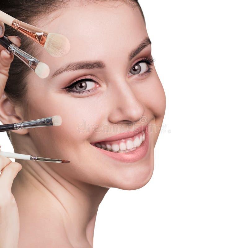 Junge Frau mit Make-upbürsten lizenzfreie stockbilder