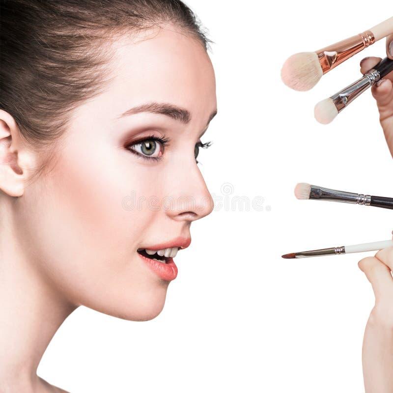 Junge Frau mit Make-upbürsten lizenzfreie stockfotografie