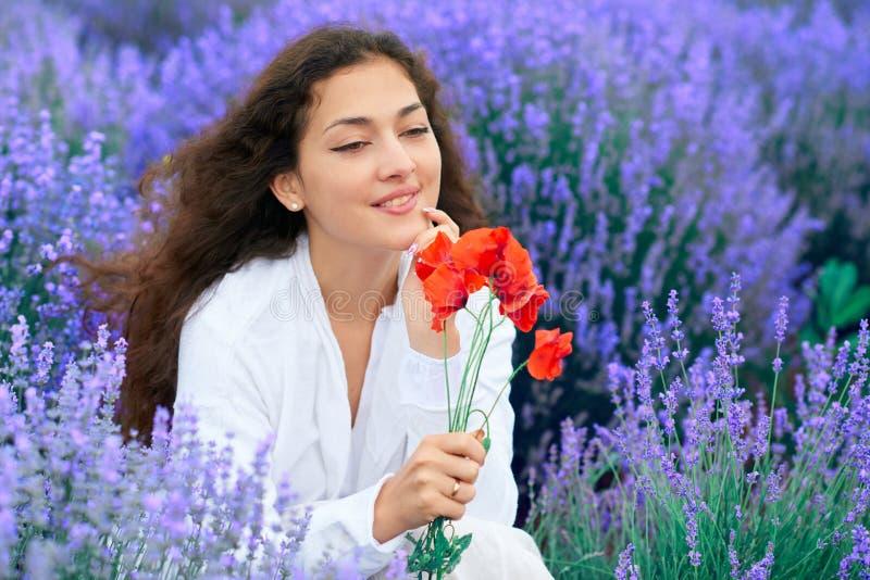 Junge Frau mit Mohnblume ist auf dem Lavendelblumengebiet, schöne Sommerlandschaft stockfotos