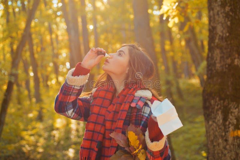 Junge Frau mit Nasenwischer nahe Herbstbaum Porträt des junge Frauen-Schnüffelnnasensprays, das ein Nasenloch schließt Frau lizenzfreies stockfoto
