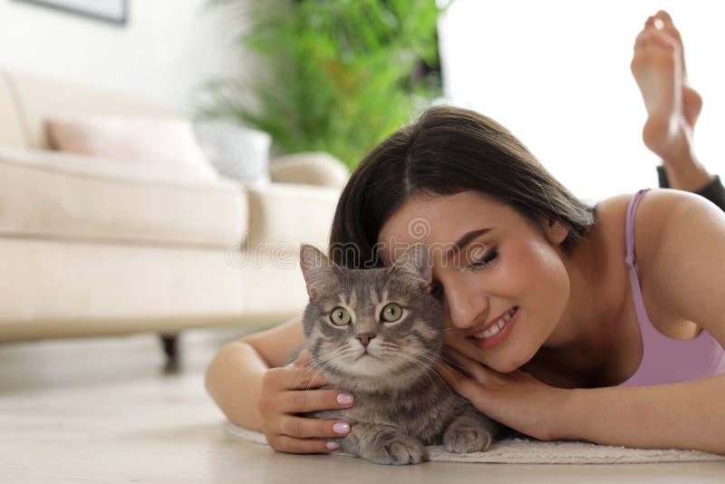 Junge Frau mit netter Katze zu Hause Haustier und Inhaber lizenzfreie stockfotografie