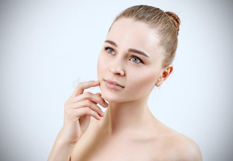 Junge Frau mit perfekter Haut träumend über blauem Hintergrund lizenzfreie stockfotos