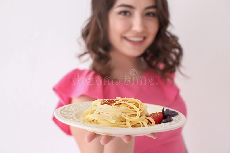 Junge Frau mit Platte von geschmackvollen Teigwaren auf weißem Hintergrund stockbilder
