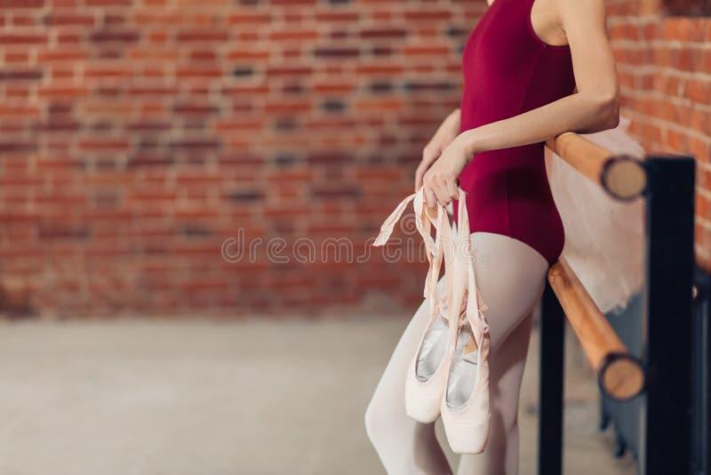 Junge Frau mit pointe Schuhen in den Händen, die auf dem Ballett Barre sich lehnen stockfoto