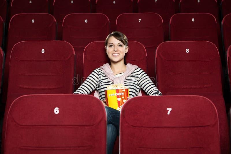Junge Frau mit Popcorn im Filmtheater lizenzfreie stockbilder